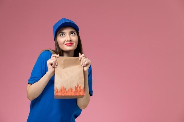 Vooraanzicht jonge vrouwelijke koerier in blauw uniform en cape met papier voedselpakket op de lichtroze muur