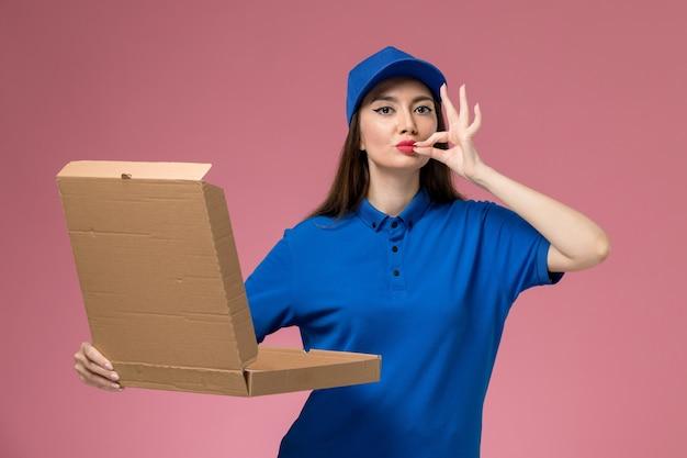 Vooraanzicht jonge vrouwelijke koerier in blauw uniform en cape met voedselleveringsdoos die het op lichtroze muurarbeider opent