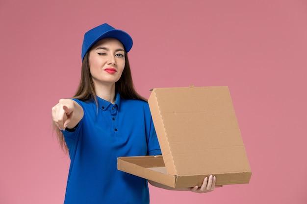 Vooraanzicht jonge vrouwelijke koerier in blauw uniform en cape met voedselleveringsdoos knipogen op roze bureau