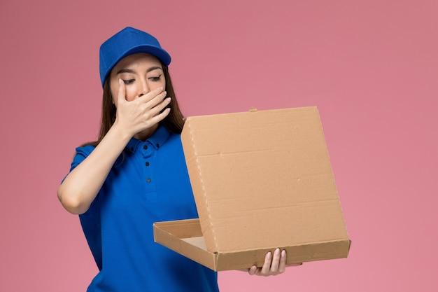 Vooraanzicht jonge vrouwelijke koerier in blauw uniform en cape voedseldoos houden en openen op roze bureau