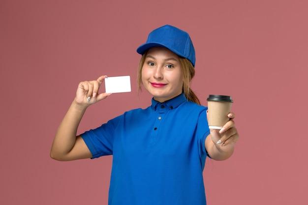 Vooraanzicht jonge vrouwelijke koerier in blauw uniform poseren bedrijf kopje koffie en witte kaart, dienst uniforme vrouw baan werknemer