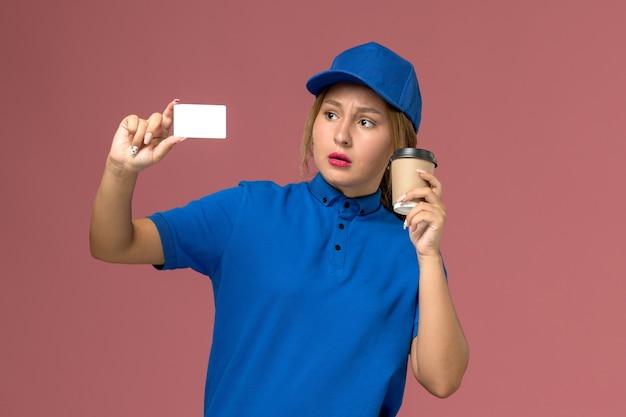 Vooraanzicht jonge vrouwelijke koerier in blauw uniform poseren bedrijf kopje koffie en witte kaart, service uniforme levering vrouw werknemer kleur