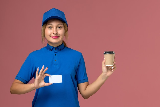 Vooraanzicht jonge vrouwelijke koerier in blauw uniform poseren met bruine levering kopje koffie, dienst uniforme levering vrouw baan