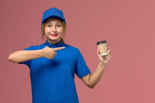 Vooraanzicht jonge vrouwelijke koerier in blauw uniform poseren met bruine levering kopje koffie op roze muur, dienst uniforme levering vrouw baan