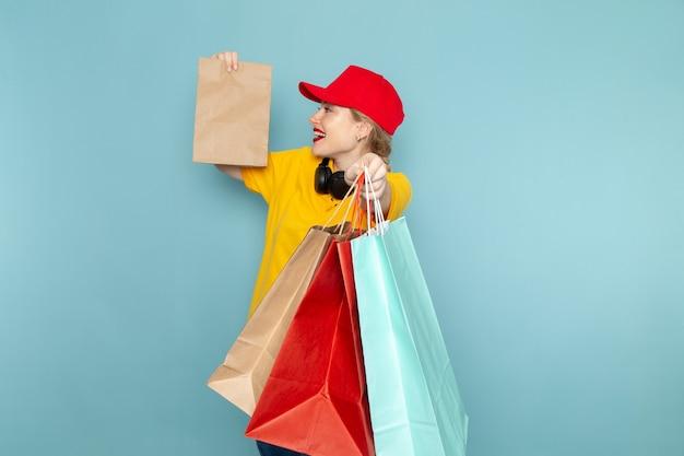 Vooraanzicht jonge vrouwelijke koerier in geel overhemd en rode cape bedrijf vermenigvuldigen en winkelen pakketten op de blauwe ruimte werken
