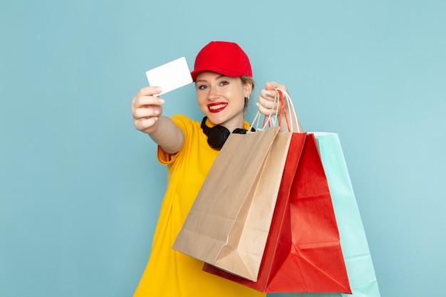 Vooraanzicht jonge vrouwelijke koerier in geel overhemd en rode cape bedrijf vermenigvuldigen en winkelen pakketten op de blauwe ruimte werknemer