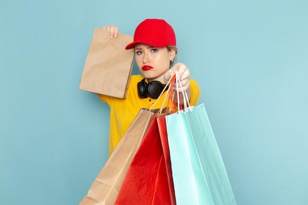 Vooraanzicht jonge vrouwelijke koerier in geel overhemd en rode cape bedrijf vermenigvuldigen en winkelen pakketten op de blauwe vloer baan