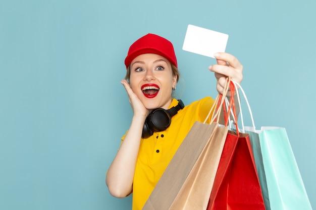 Vooraanzicht jonge vrouwelijke koerier in geel overhemd en rode cape bedrijf vermenigvuldigt het winkelen pakketten met kaart op de blauwe ruimtebaan