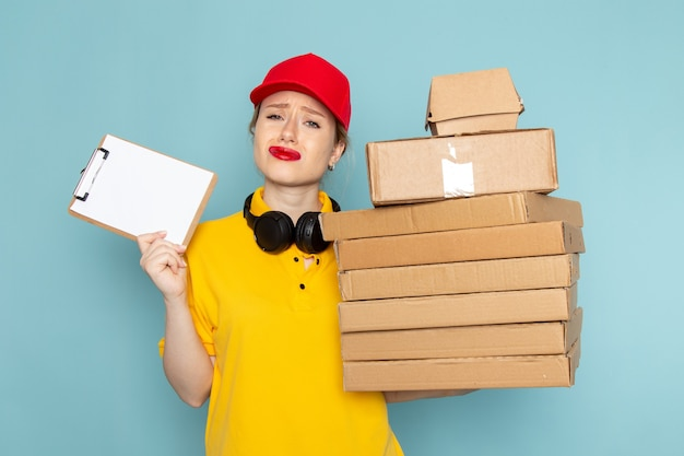 Vooraanzicht jonge vrouwelijke koerier in geel overhemd en rode cape bedrijf vermenigvuldigt pakketten en blocnote op de blauwe ruimte