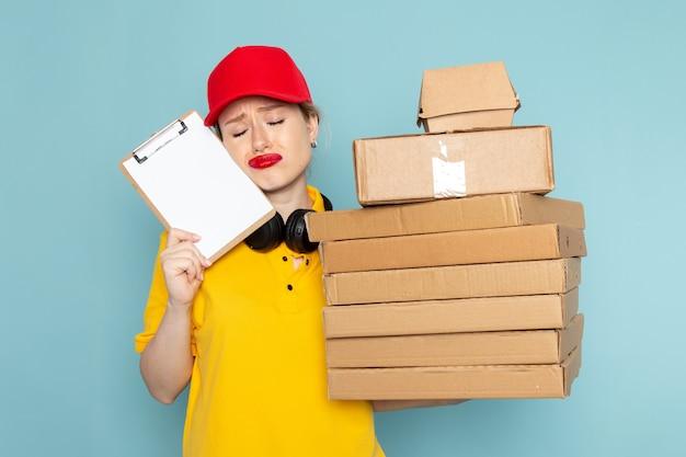 Vooraanzicht jonge vrouwelijke koerier in geel overhemd en rode cape bedrijf vermenigvuldigt pakketten en blocnote op het blauwe ruimtewerk