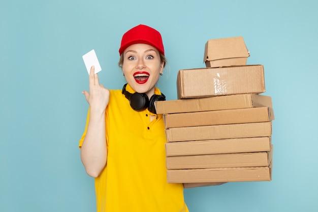 Vooraanzicht jonge vrouwelijke koerier in geel overhemd en rode cape bedrijf vermenigvuldigt pakketten en witte kaart op de blauwe ruimte