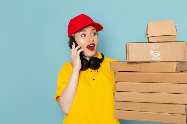 Vooraanzicht jonge vrouwelijke koerier in geel overhemd en rode cape bedrijf vermenigvuldigt pakketten talkign aan de telefoon op de blauwe ruimtebaan