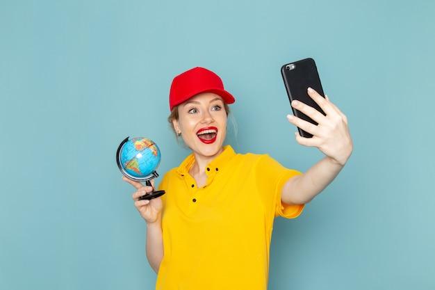 Vooraanzicht jonge vrouwelijke koerier in geel overhemd en rode cape die een selfie met bol glimlachen op de blauwe ruimte
