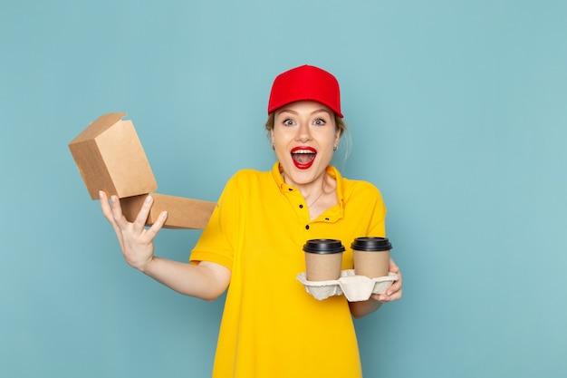 Vooraanzicht jonge vrouwelijke koerier in geel overhemd en rode cape die plastic koffiekopjes en voedselpakket houden die op de blauwe ruimtebaan glimlachen