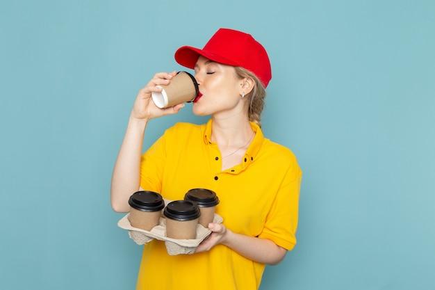 Vooraanzicht jonge vrouwelijke koerier in geel overhemd en rode cape met koffiekopjes drinken op de blauwe ruimte werknemer