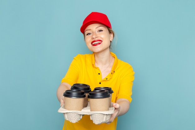 Vooraanzicht jonge vrouwelijke koerier in geel overhemd en rode cape met koffiekopjes glimlachend op de blauwe ruimte werknemer