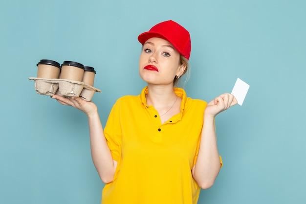 Vooraanzicht jonge vrouwelijke koerier in geel overhemd en rode cape met plastic koffiekopjes witte kaart op de blauwe ruimte werkbaan