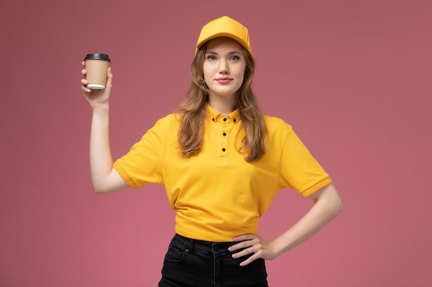 Vooraanzicht jonge vrouwelijke koerier in geel uniform bedrijf plastic bezorging koffie op roze bureau baan uniforme bezorgdienst werknemer