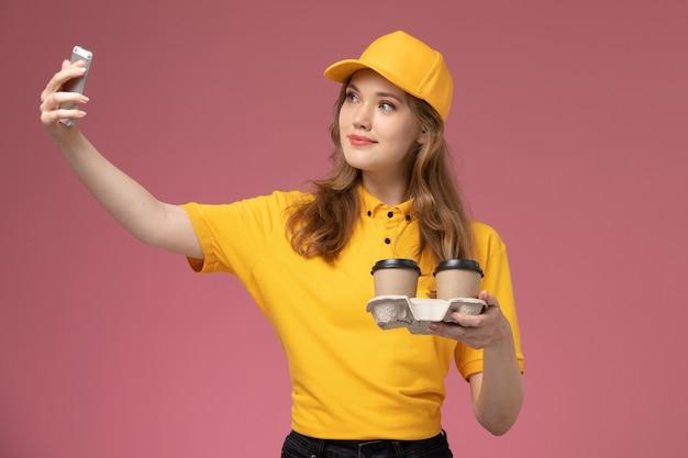 Vooraanzicht jonge vrouwelijke koerier in geel uniform koffiekopjes vasthouden en foto met hen maken op het donkerroze bureau uniforme bezorgdienst werknemer