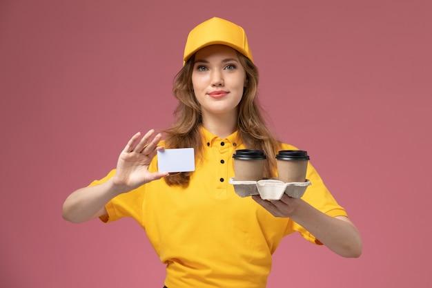 Vooraanzicht jonge vrouwelijke koerier in geel uniform met bruine koffie plastic bekers samen met witte kaart op de donkerroze bureau uniforme levering dienst vrouwelijke werknemer