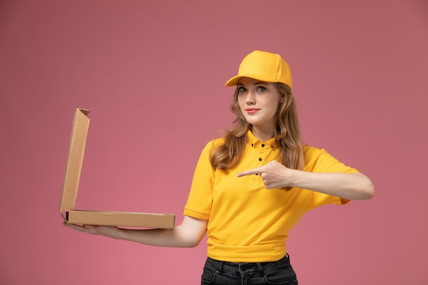 Vooraanzicht jonge vrouwelijke koerier in geel uniform met bruine voedseldoos die het opent op het donkerroze bureau uniforme bezorgdienst vrouwelijke werknemer