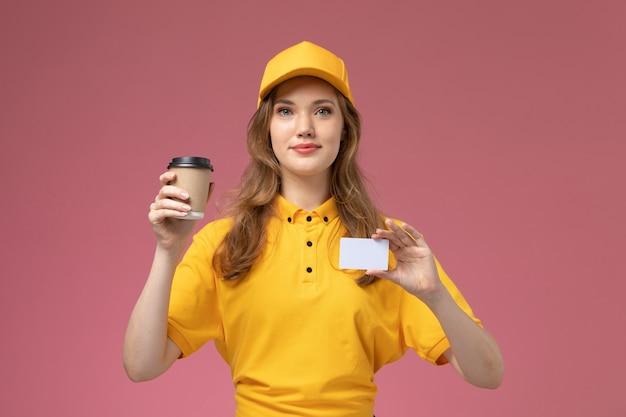 Vooraanzicht jonge vrouwelijke koerier in geel uniform met koffiekopje en witte kaart op het donkerroze bureau uniforme levering baan dienstverlener