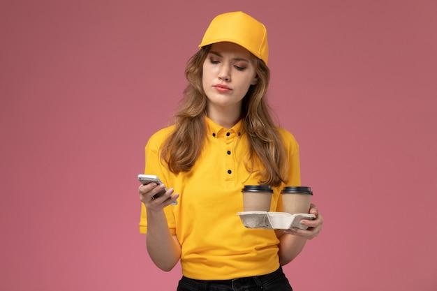 Vooraanzicht jonge vrouwelijke koerier in geel uniform met koffiekopjes tijdens het gebruik van haar telefoon op roze achtergrond bureau baan uniforme bezorgdienst werknemer