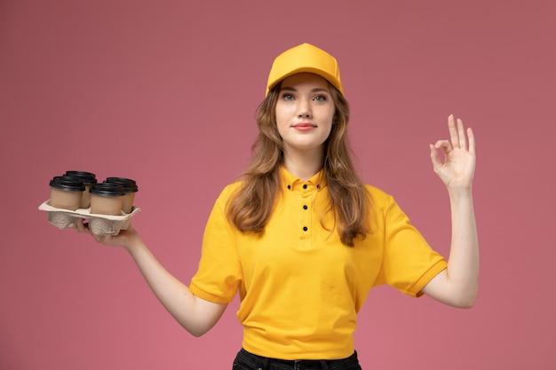 Vooraanzicht jonge vrouwelijke koerier in geel uniform met plastic bruine koffiekopjes met schattige uitdrukking op roze achtergrond baan uniforme levering kleur dienstverlener