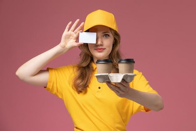 Vooraanzicht jonge vrouwelijke koerier in geel uniform met plastic koffiekopjes met witte kaart op donkerroze bureau uniforme levering baan dienstverlener
