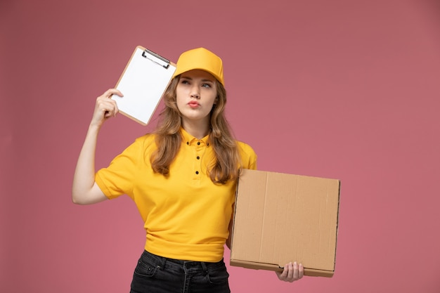 Vooraanzicht jonge vrouwelijke koerier in geel uniform met voedseldoos en blocnote denken aan de donkerroze bureau baan uniforme bezorgdienst werknemer