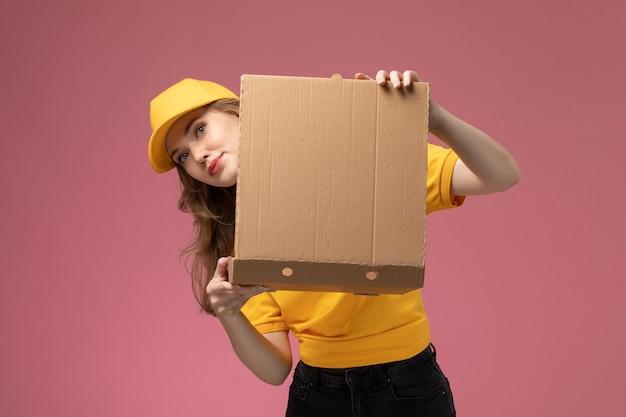 Vooraanzicht jonge vrouwelijke koerier in gele uniform gele cape met voedsel bezorgdoos met glimlach op de donkerroze achtergrond uniforme levering dienst vrouwelijke werknemer