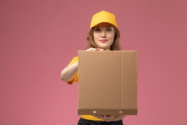 Vooraanzicht jonge vrouwelijke koerier in gele uniform gele cape met voedsel bezorgdoos openen op de donkerroze achtergrond uniforme bezorgdienst vrouwelijke werknemer
