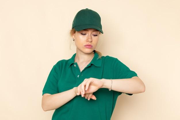 Vooraanzicht jonge vrouwelijke koerier in groen uniform en groene cape die haar pols op de lichte ruimte bekijkt