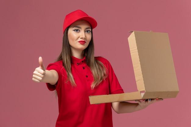 Vooraanzicht jonge vrouwelijke koerier in rode uniform bedrijf levering voedsel doos poseren op lichtroze achtergrond dienst levering uniforme bedrijfsmedewerker