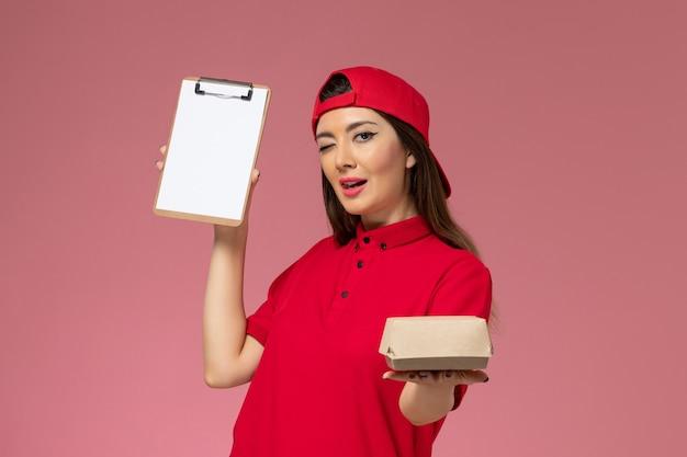 Vooraanzicht jonge vrouwelijke koerier in rode uniforme cape met weinig voedselpakket en blocnote op haar handen op de roze muur