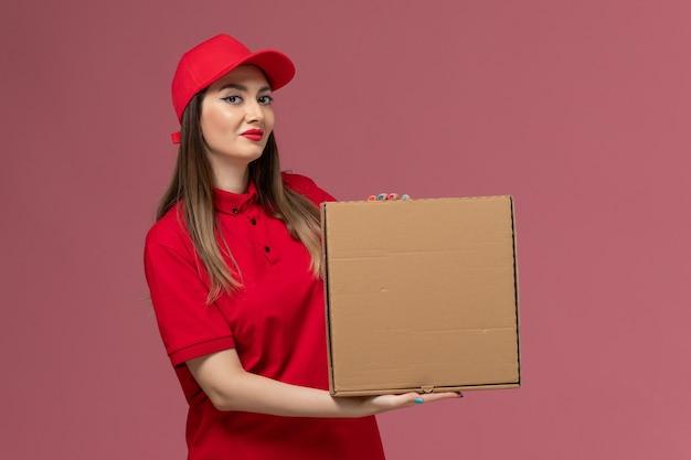 Vooraanzicht jonge vrouwelijke koerier in rode uniforme levering voedsel doos met glimlach op roze achtergrond service levering baan uniform bedrijf