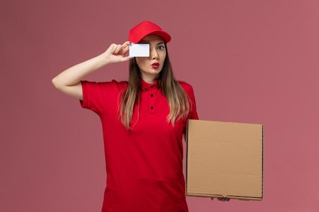 Vooraanzicht jonge vrouwelijke koerier in rode uniforme levering voedseldoos en witte kaart op lichtroze achtergrond levering dienst uniforme bedrijf baan