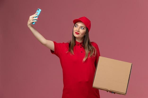 Vooraanzicht jonge vrouwelijke koerier in rode uniforme levering voedseldoos houden en het nemen van foto ermee op roze achtergrond bezorgdienst uniform bedrijf