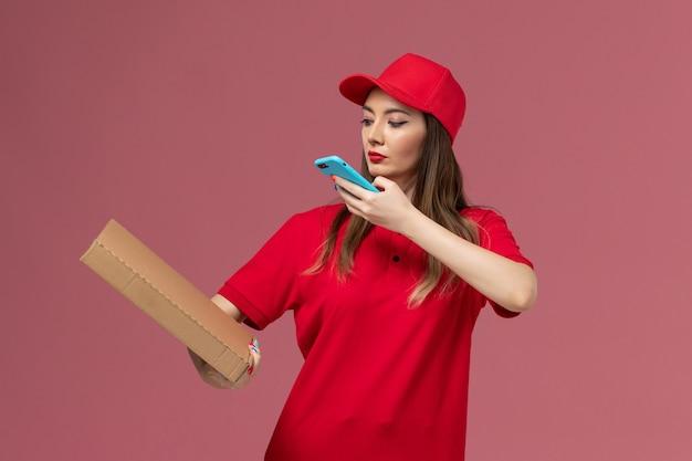 Vooraanzicht jonge vrouwelijke koerier in rode uniforme levering voedseldoos houden en het nemen van foto ervan op roze achtergrond bezorgdienst uniform bedrijf