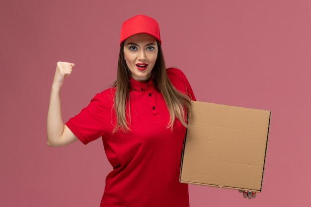 Vooraanzicht jonge vrouwelijke koerier in rode uniforme levering voedseldoos juichen op de roze achtergrond service levering uniform bedrijf