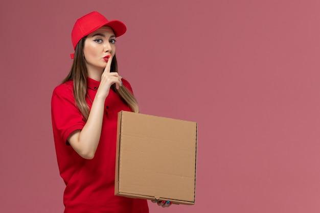 Vooraanzicht jonge vrouwelijke koerier in rode uniforme levering voedseldoos onpink achtergrond service levering uniform