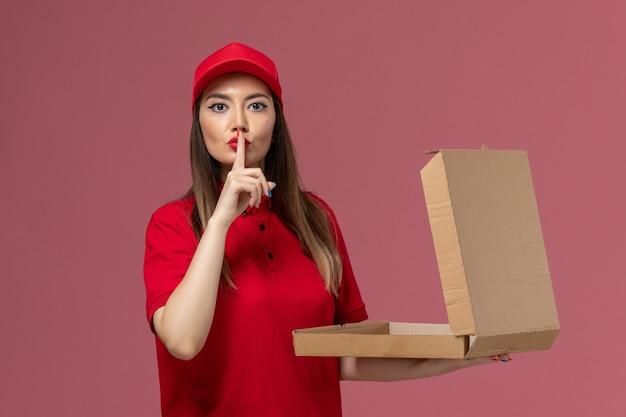 Vooraanzicht jonge vrouwelijke koerier in rode uniforme levering voedseldoos op de roze achtergrond service levering uniforme bedrijfsmedewerker