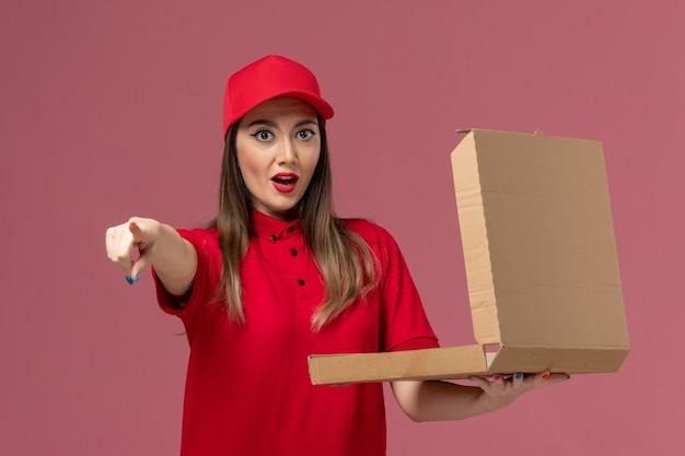 Vooraanzicht jonge vrouwelijke koerier in rode uniforme levering voedseldoos op het lichtroze bureau service levering baan uniform bedrijf