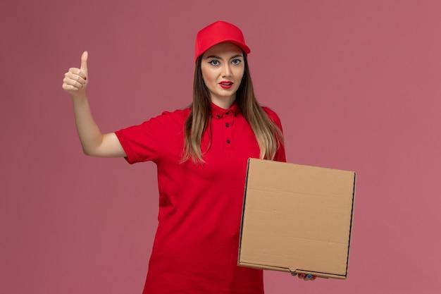Vooraanzicht jonge vrouwelijke koerier in rode uniforme levering voedseldoos op het roze achtergrond service levering uniform bedrijf
