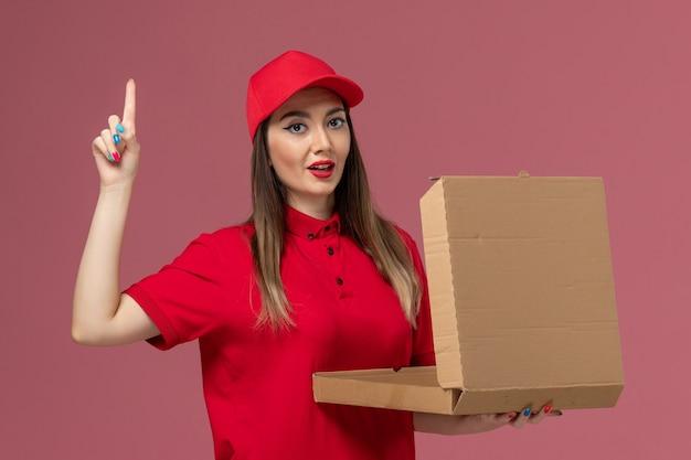 Vooraanzicht jonge vrouwelijke koerier in rode uniforme levering voedseldoos op het roze bureau service levering uniform bedrijf