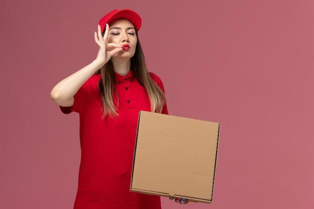 Vooraanzicht jonge vrouwelijke koerier in rode uniforme levering voedseldoos op lichtroze achtergrond service levering uniform bedrijf