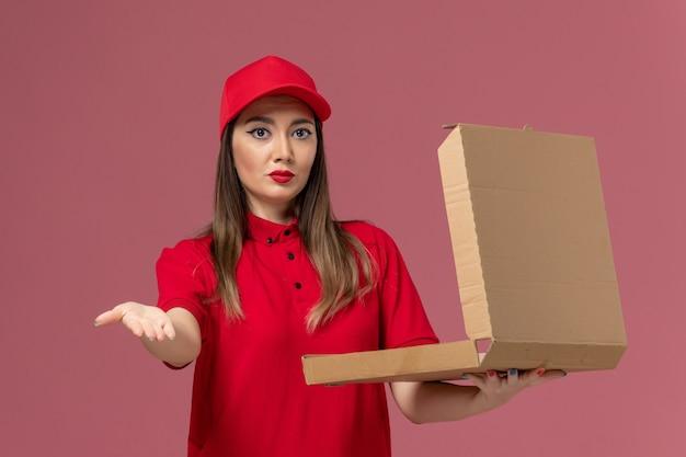 Vooraanzicht jonge vrouwelijke koerier in rode uniforme levering voedseldoos op lichtroze achtergrond service levering uniform werknemer bedrijf