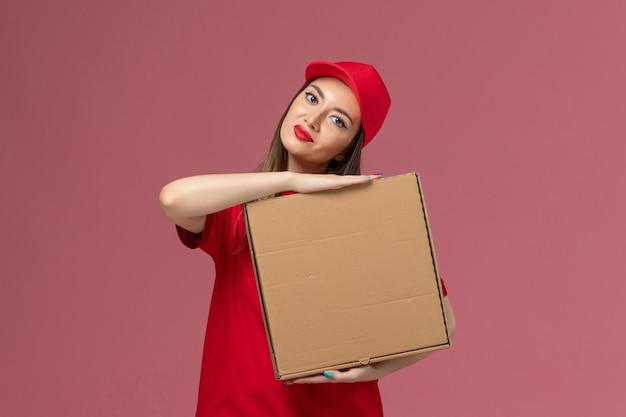 Vooraanzicht jonge vrouwelijke koerier in rode uniforme levering voedseldoos op roze vloer service levering uniform bedrijf