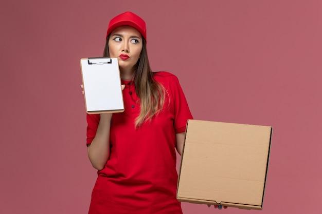 Vooraanzicht jonge vrouwelijke koerier in rode uniforme voedseldoos met blocnote en denken op roze achtergrond bezorgdienst uniform bedrijf baan werk