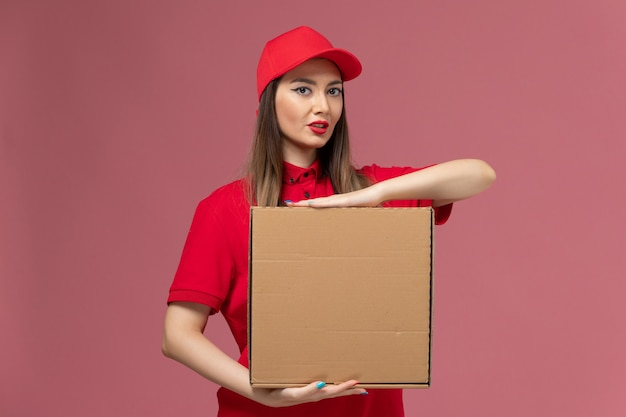 Vooraanzicht jonge vrouwelijke koerier in rode uniforme voedseldoos op roze achtergrond werknemer dienstverlening levering uniform bedrijf baan